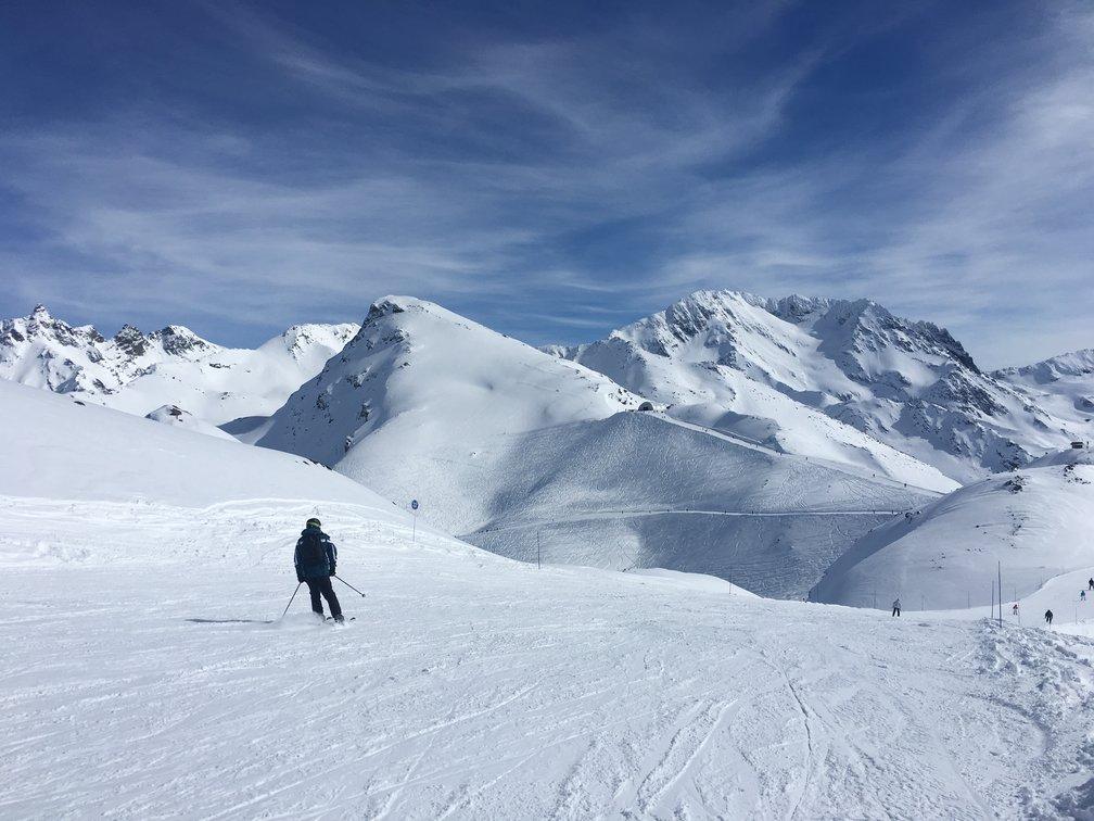 Mann står på ski ned fjell